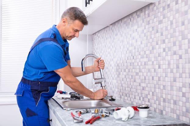 plumber fixing hard water damage faucet
